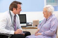 获得帮助的年长妇女从英国GP 免版税图库摄影