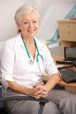 GP británico de la hembra que se sienta en el escritorio Foto de archivo libre de regalías