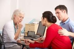 GP britannico che comunica con coppie ansiose nella chirurgia Immagini Stock