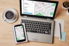 GPS在膝上型计算机和智能手机屏幕上的地图航海app 地点 免版税库存照片