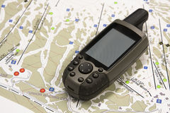 GPS. A handheld global positioning unit sits on a topo map.  The screen is blank and ready for your text Royalty Free Stock Images
