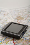 GPS device on a map. GPS unit seated on a road map Stock Image
