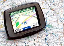 GPS or Map. Portable GPS for a car sitting on a map stock image