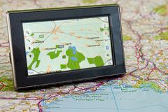 GPS And Map. Portable GPS for a car sitting on a map royalty free stock image