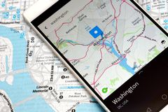 GPS navigation map smartphone. Modern smartphone with navigation system in Washington. Classical map vs. GPS navigation application in smartphone Royalty Free Stock Images