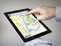 Gps navigation on a tablet. Route planner concept: hands with touchscreen tablet with gps navigation app on the screen. Screen graphics are made up Royalty Free Stock Image