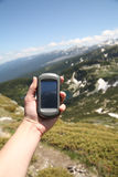 Gps navigator. Hand holding GPS navigator mountain background as the background Stock Photo