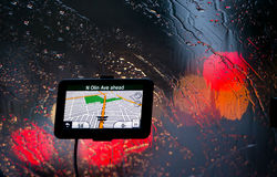 GPS navigator in rain and lights headlights on glass Stock Photos