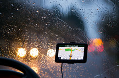 GPS navigator in raining glass and taillights headlights royalty free stock photography