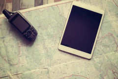GPS navigator and tablet are on the paper map Stock Image