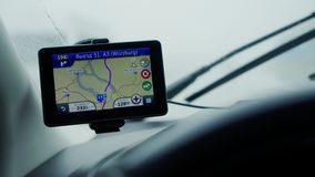 GPS Navigator on the windshield of the car in rainy day. Travel wih the Navigator. Using tablet for GPS navigation to stock video