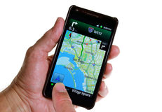 GPS Road Navigation by Smartphone. A hand holding a smartphone with a GPS navigation map Stock Images