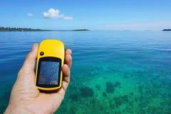 GPS satellit- navigatör i hand ovanför klart vatten Arkivbilder