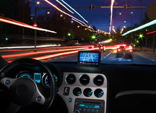 Gps satellite navigator in car. Night view of navigating with gps satellite navigator in traffic seen from car cabin Royalty Free Stock Photo