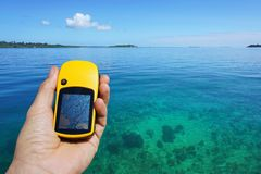 GPS satellite navigator in hand above clear water Stock Images