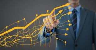 Gráfico amarelo tocante da seção meados de do homem de negócio contra o fundo cinzento Foto de Stock Royalty Free