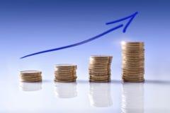 Gráfico ascendente do negócio representado com as moedas e o backgro azul Fotos de Stock Royalty Free