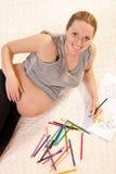 Gráfico bastante prengnant de la mujer con los lápices Foto de archivo libre de regalías