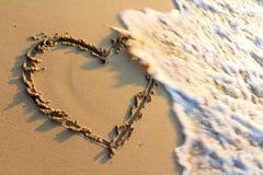 Gráfico de la mano de la dimensión de una variable del corazón en una playa Fotos de archivo libres de regalías