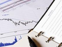 Gráfico de las finanzas que cae y una libreta Fotos de archivo libres de regalías