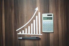 Gráfico de papel do crescimento com calculadora e pena no fundo de madeira Foto de Stock Royalty Free