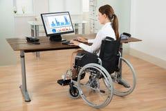 Gráfico de On Wheelchair Analyzing da mulher de negócios Fotografia de Stock Royalty Free