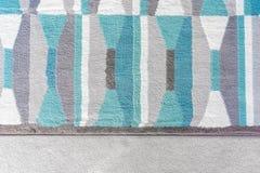 Gráfico del fondo, vista superior de una manta geométrica con los modelos azules y grises del color, encima de una alfombra beige foto de archivo