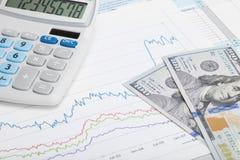 Gráfico del mercado de acción con 100 dólares de billete de banco y calculadora Fotos de archivo libres de regalías