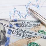 Gráfico del mercado de acción con la pluma y cientos dólares de billete de banco - ascendente cercano Fotografía de archivo