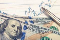 Gráfico del mercado de acción con la pluma y cientos dólares de billete de banco - tiro ascendente cercano Imagen filtrada: efect Foto de archivo libre de regalías