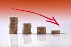 Gráfico hacia abajo del negocio representado con las monedas y el CCB anaranjado Fotos de archivo libres de regalías