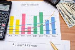 Gráficos, cartas, tabla del negocio con el dinero, calculadora y pluma Fotos de archivo