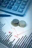 Gráficos con la pluma y calculadora y monedas Fotografía de archivo libre de regalías