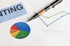 Gráficos de color y economía del negocio con una pluma Foto de archivo