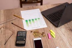 gráficos de la inversión con el ordenador portátil y la calculadora Imágenes de archivo libres de regalías