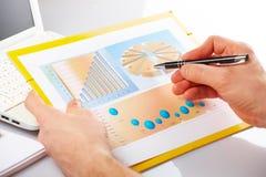 Gráficos de negócio e mãos masculinas imagem de stock