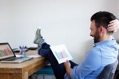 Gráficos de negócio relaxado da leitura do homem no escritório Fotos de Stock Royalty Free