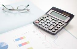 Gráficos de negocio con una calculadora Foto de archivo
