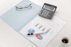 Gráficos de negocio con una calculadora, una pluma y los vidrios Foto de archivo