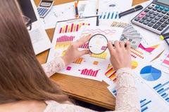 Gráficos de negocio del analista que magnifican en oficina, imagen de archivo libre de regalías