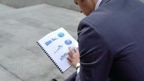 Gráficos de negocio de examen del consultor financiero pensativo, compañía que se arruina imágenes de archivo libres de regalías