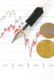 Gráficos del mercado de acción con las monedas de la pluma y del euro Fotos de archivo