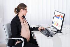 Gráficos embarazadas de Looking At Financial de la empresaria fotos de archivo libres de regalías