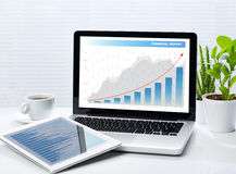 Gráficos financeiros no portátil e na tabuleta Imagens de Stock