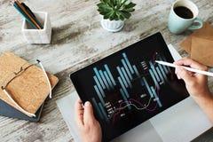 Gráficos financieros en la pantalla del dispositivo Concepto en línea de la inversión y de la compra y venta de acciones foto de archivo libre de regalías