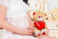 Grávido em um vestido branco do laço com o urso de peluche Imagem de Stock