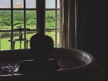 Âgrâ, uttar pradesh, Inde 9 août 2018 : Une femme prend un bain de luxe dans l'eau rose et des pétales de rose à la station therm image stock