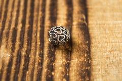 Grânulo de prata para o bracelete no fundo de madeira foto de stock
