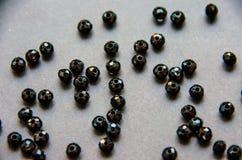 Grânulos coloridos, pretos e pedras isolados no fundo cinzento imagem de stock