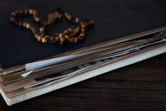 Grânulos de madeira do rosário em livros velhos Fundo de madeira fotografia de stock